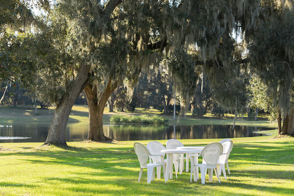 White plastic table and chairs outside in a garden on green lawn by a pond or lake in the afternoon sun and a peaceful relaxing serene tranquil setting